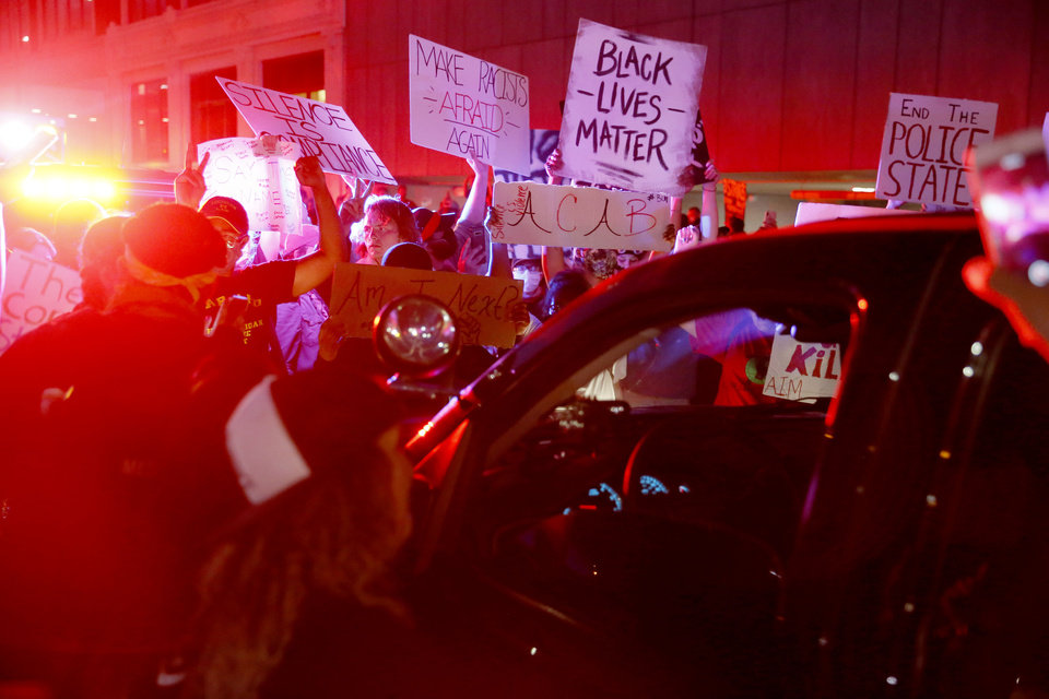 Photo - Protesters block a law enforcement vehicle after a President Donald Trump rally at the BOK Center in Tulsa, Okla., Saturday, June 20, 2020. [Bryan Terry/The Oklahoman]