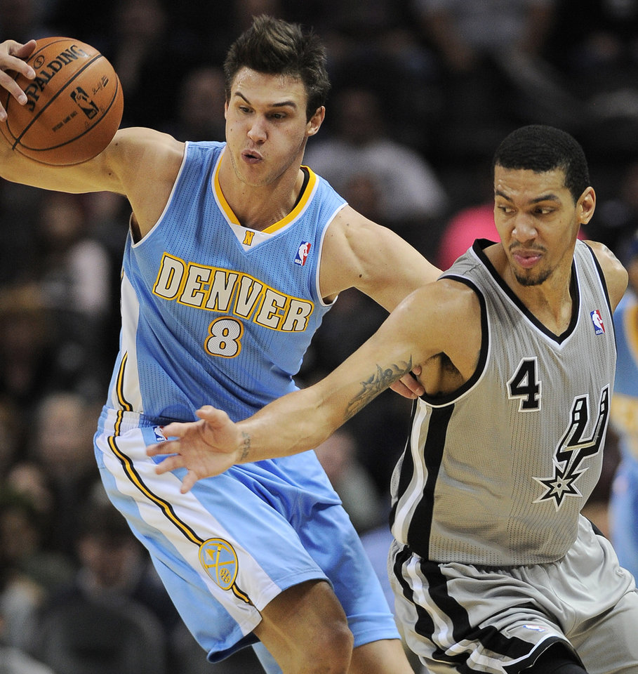 Denver Nuggets' Danilo Gallinari, left, of Italy, grabs a loose ball behind San Antonio Spurs' Danny Green during the first half of an NBA basketball game, Saturday, Nov. 17, 2012, in San Antonio. (AP Photo/Darren Abate)