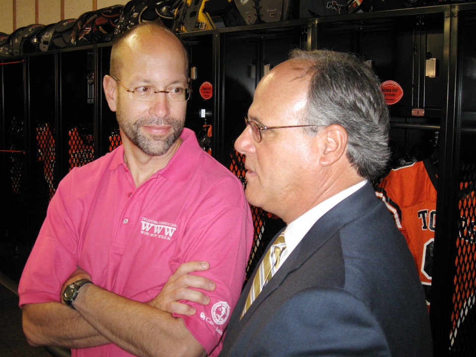 Photo - Robert Mannel, left, director of the University of Oklahoma Cancer Institute, chats with Norman Superintendent Joe Siano Monday at Norman High School following an announcement of the Oklahoma Students Care
