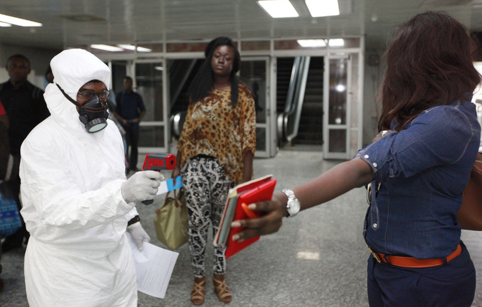 Photo - A passenger holds personal possessions as a Nigerian port health official uses a thermometer on her at the arrivals hall of Murtala Muhammed International Airport in Lagos, Nigeria, Wednesday Aug. 6, 2014. A Nigerian nurse who treated a man with Ebola is now dead and five others are sick with one of the world's most virulent diseases, authorities said Wednesday as the death toll rose to at least 932 people in four West African countries. (AP Photo/Sunday Alamba)