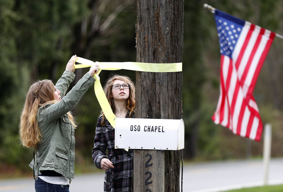 Photo - Randi Ray, daughter of Oso Community Chapel's pastor Gary Ray, and Gary's daughter-in-law Molly Ray, right, put up yellow ribbons around the Chapel grounds on Sunday, March 30, 2014 before their 10am service. Periods of rain and wind have hampered efforts the past two days, with some rain showers continuing today. Last night, the confirmed fatalities list was updated to 18, with the number of those missing falling from 90 to 30.  (AP Photo/The Seattle Times, Lindsey Wasson) MANDATORY CREDIT