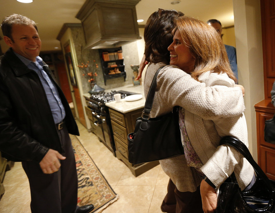 Photo - Jody Smith , left, and Terri Angier hug beside Greg Smith on Nov. 19 as guests greet each other before a dinner between people of different faiths in Edmond. The dinner is part of the Amazing Faiths project by the Interfaith Alliance of Oklahoma, bringing together people of different faiths for dinner and interfaith conversation. Photo by Bryan Terry, The Oklahoman  BRYAN TERRY - THE OKLAHOMAN