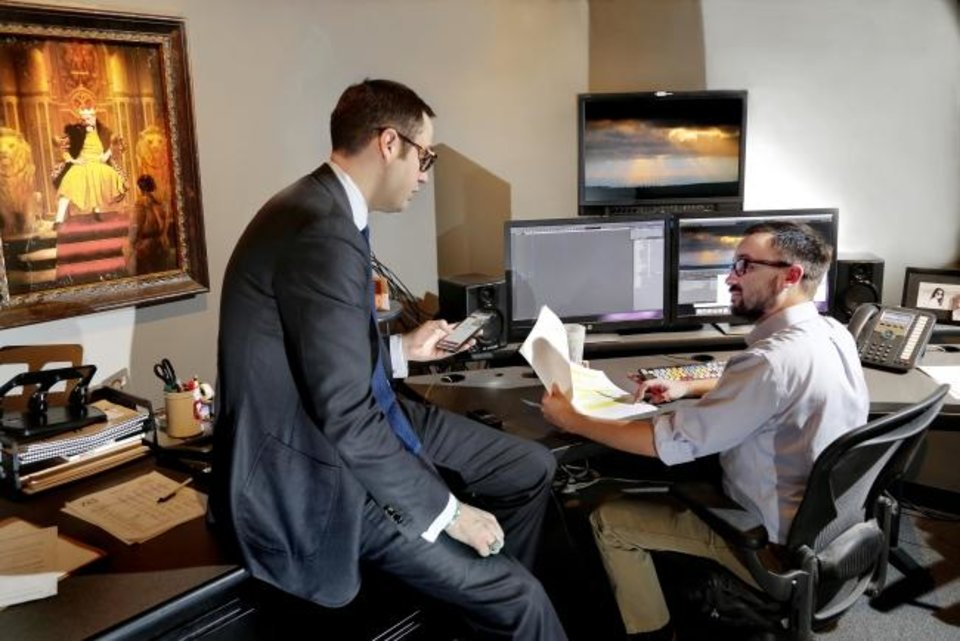 Photo -  Revan McQueen, left, and Charlie Ryan, a video editor, visit in one of the editing rooms Ackerman McQueen.  McQueen, CEO, announced in January his company will be moving to the Monarch building in Midtown. [JIM BECKEL/THE OKLAHOMAN ARCHIVES]