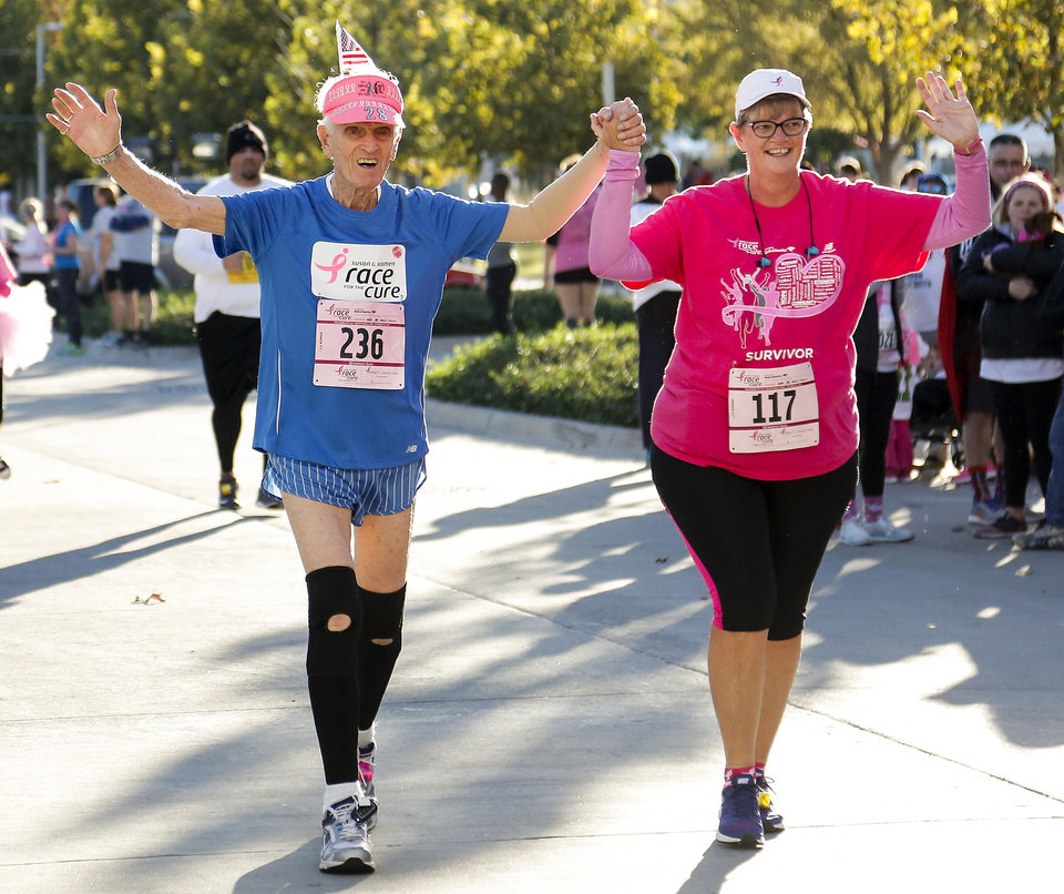 Photo -  Male breast cancer survivor Mark Goldstein runs hand in hand with survivor Kathy Sikes as they near the finish line during the 23rd annual Oklahoma City Susan G. Komen Race for the Cure at the Civic Center in Oklahoma City on Saturday. The Oklahoma City race was Goldstein's 236th race he has participated in. [Photo by Chris Landsberger, The Oklahoman]