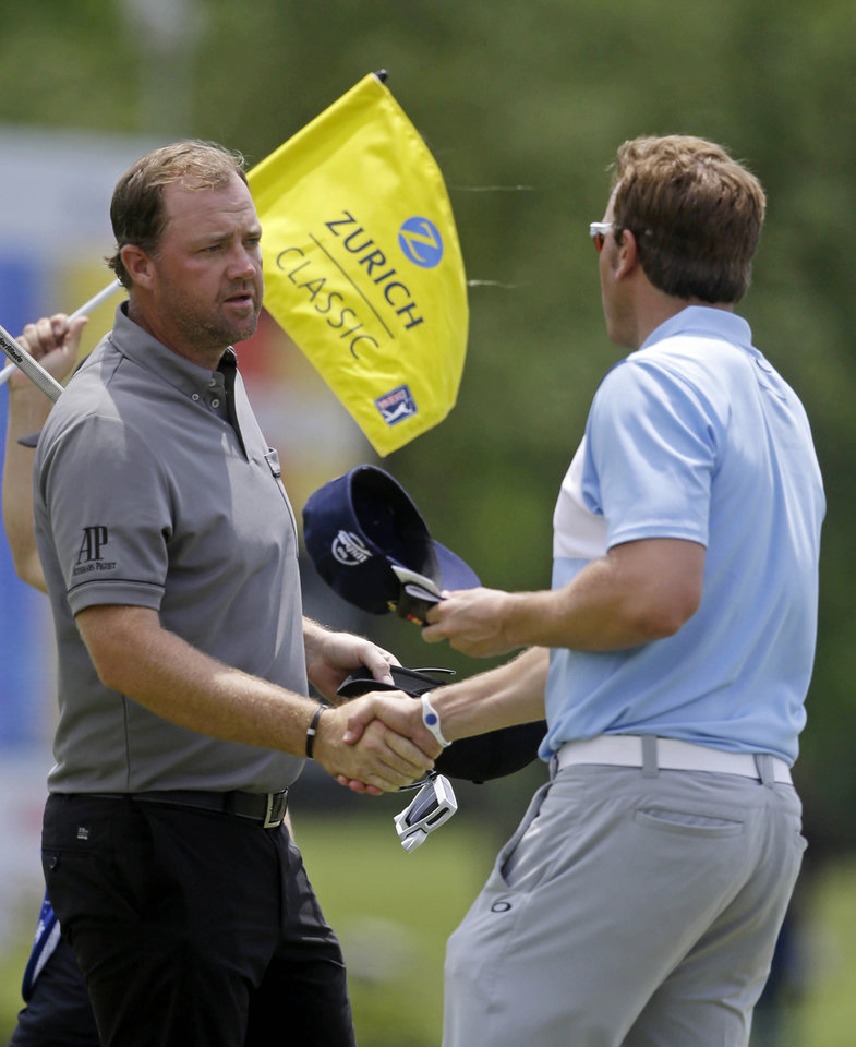 Photo - Peter Hanson, left, of Sweden, shakes hands with Ricky Barnes on the ninth green as they finished the opening round of the Zurich Classic golf tournament at TPC Louisiana in Avondale, La., Thursday, April 24, 2014. (AP Photo/Gerald Herbert)