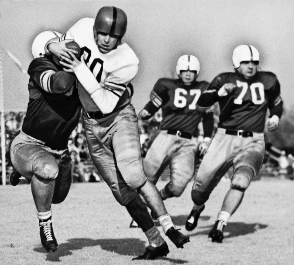 Wade Walker, University of Oklahoma tackle, tries tackling the ball from Aggie Bill Long Saturday at Norman in 1947. Dark-shirted Sooner guards, Paul (Buddy) Burris (No. 67) and Dee Andros (70) trail Long, who elected to run when his pass receivers were covered, gaining five yards. OKLAHOMAN ARCHIVE PHOTO