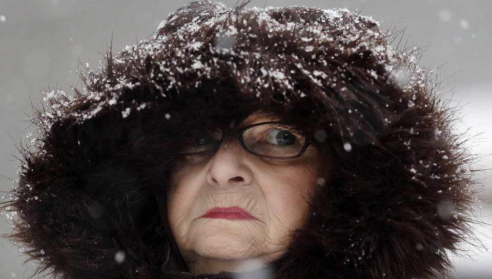 Photo - Mary Ann Bova walks along a slippery snow-covered sidewalk during a winter storm in Buffalo, N.Y., Friday, Feb. 8, 2013. In some upstate areas, snow fell early Friday morning and was expected to increase throughout the day, with the heaviest accumulations expected in eastern New York on Friday night.(AP Photo/David Duprey)