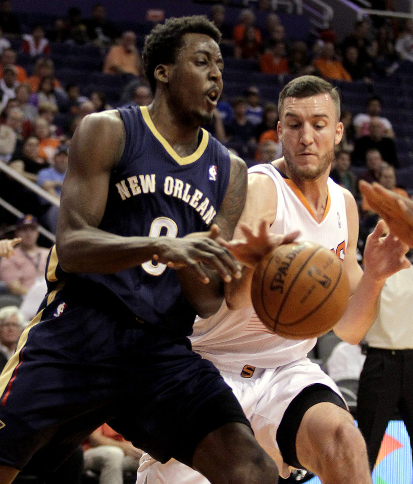 Photo - Phoenix Suns center Miles Plumlee (22), right, knocks the ball away from New Orleans Pelicans small forward Al-Farouq Aminu (0) in the first quarter during an NBA basketball game on Sunday, Nov. 10, 2013, in Phoenix. (AP Photo/Rick Scuteri)