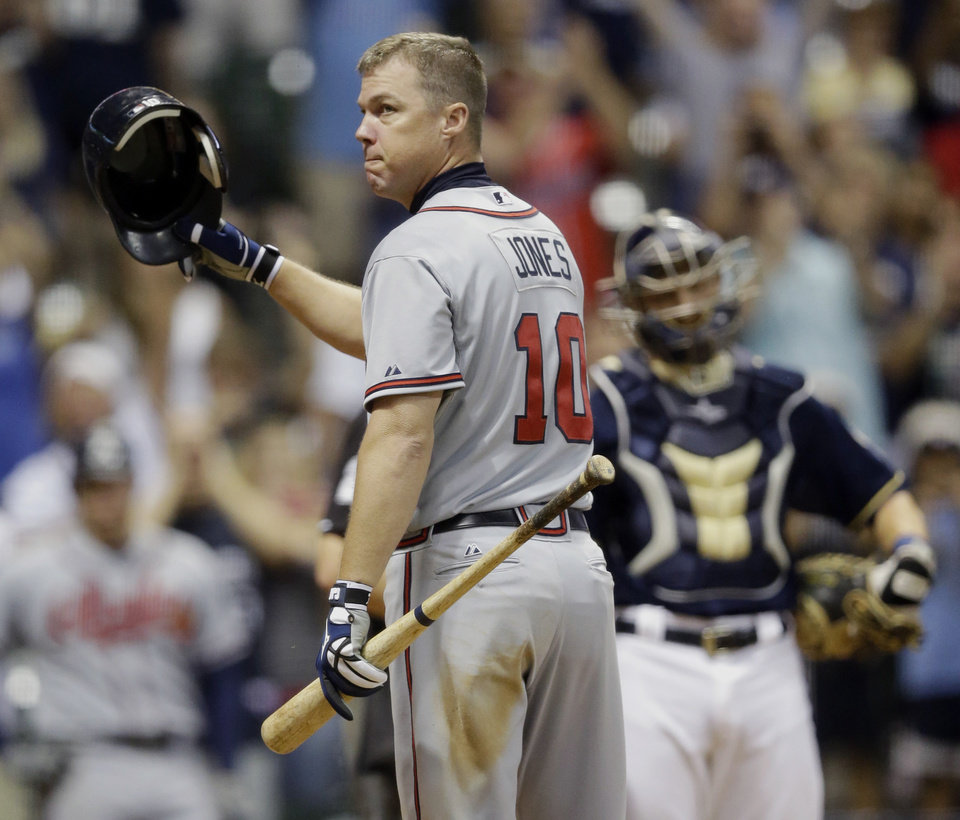 Photo -   Milwaukee Brewers catcher Jonathan Lucroy watches as Atlanta Braves' Chipper Jones acknowledges the crowd for his last at bat at Miller Park during the ninth inning of a baseball game Wednesday, Sept. 12, 2012, in Milwaukee. (AP Photo/Morry Gash)