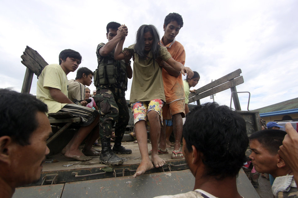 A resident who was rescued from her flooded home is assisted as she alights from a military truck in New Bataan, Compostela Valley province, southern Philippines on Wednesday Dec. 5, 2012. The death toll from Typhoon Bhopa climbed to more than 100 people Wednesday, while scores of others remain missing in the worst-hit areas of the southern Philippines. (AP Photo/Karlos Manlupig)