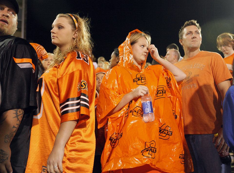 Photo - Ashley Davidson, right, and other Oklahoma State fans keep an eye on the storm as it delays the start of the game between Oklahoma State and Tulsa on Saturday. Photo by Chris Landsberger, The Oklahoman