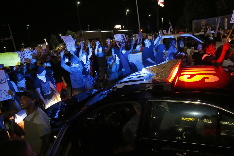 Photo - Protesters surround an Oklahoma City Police car near NW 23rd and Penn in Oklahoma City, Saturday, May 30, 2020. The protest was in response to the death of George Floyd. [Sarah Phipps/The Oklahoman]