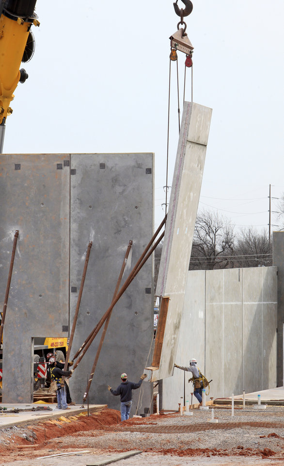 Photo -  Construction workers raise a concrete panel Wednesday while putting up a wall at the Center of Hope being built by the Salvation Army Central Oklahoma Area Command at NW 10 and Pennsylvania Avenue in Oklahoma City. Photo by Paul B. Southerland, The Oklahoman   PAUL B. SOUTHERLAND -