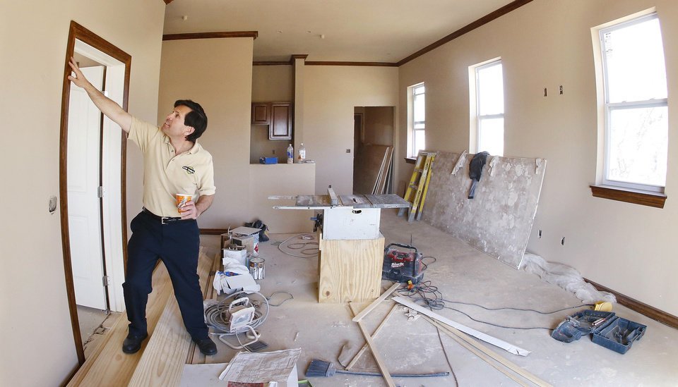 Schlotzsky�s franchisee David Jones inspects wood trim around the door to a bedroom in one of four apartmens being built above his new location in Midwest City. Photo by Jim Beckel, THE OKLAHOMAN