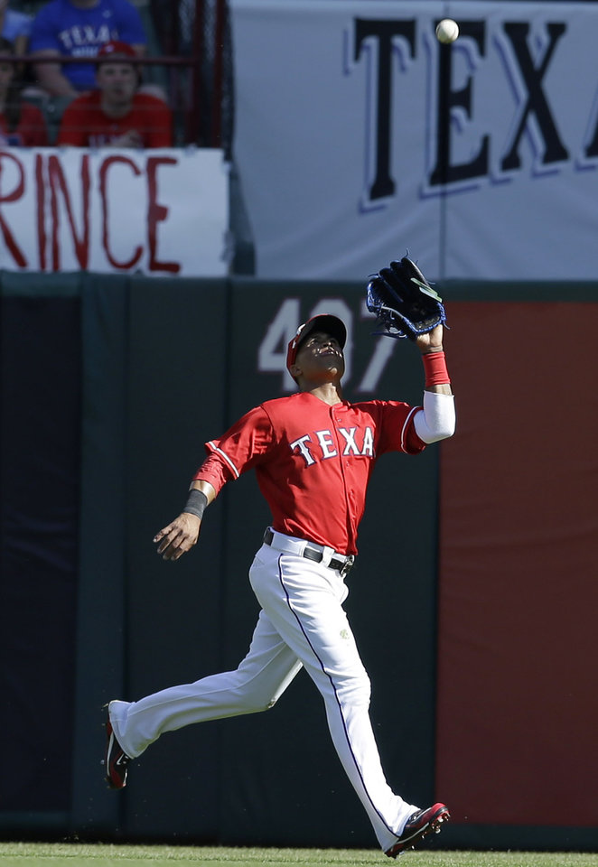 Photo - Texas Rangers center fielder Leonys Martin catches a fly ball against the Philadelphia Phillies during the ninth inning of an opening day baseball game at Globe Life Park, Monday, March 31, 2014, in Arlington, Texas. The Phillies won 14-10. (AP Photo/Tony Gutierrez)