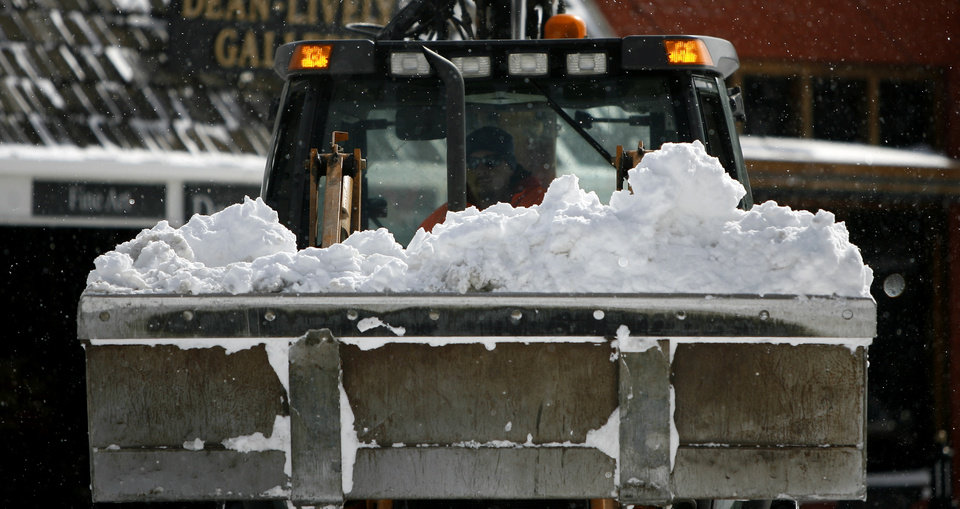 Photo - A front end loader clears snow from downtown Edmond, Okla., on Wednesday, Feb. 9, 2011.  Photo by Bryan Terry, The Oklahoman