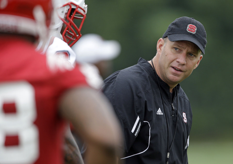 Photo - North Carolina State coach Dave Doeren watches his players during the team's first NCAA college football practice of the season in Raleigh, N.C., Saturday, Aug. 2, 2014. (AP Photo/Gerry Broome)