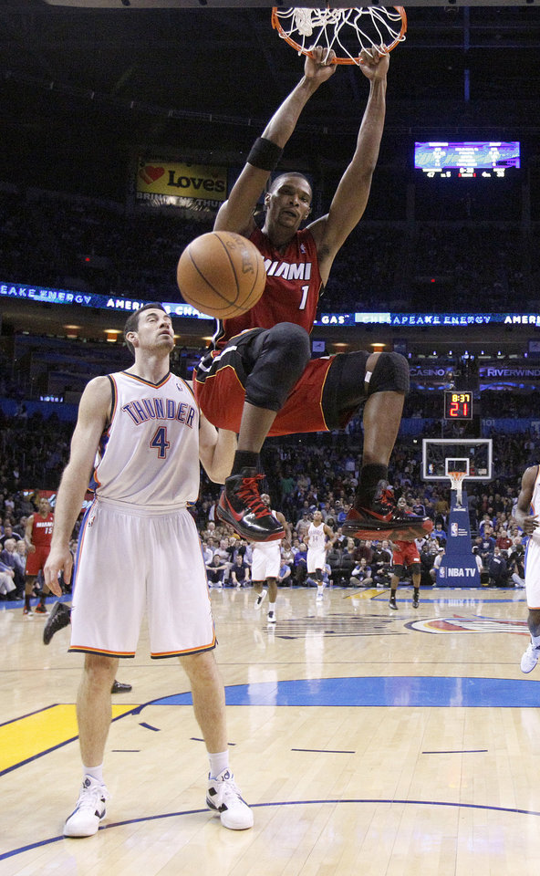 Photo - Miami's Chris Bosh (1) dunks in front of Oklahoma City's Nick Collison (4) during the NBA basketball game between Oklahoma City and Miami at the OKC Arena in Oklahoma City, Thursday, Jan. 30, 2011. Photo by Sarah Phipps, The Oklahoman
