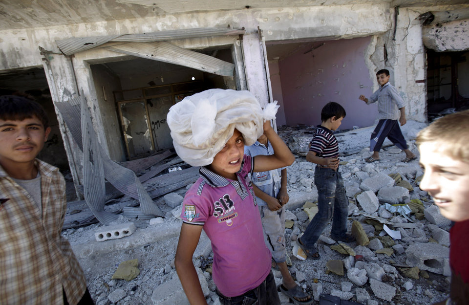 Photo -   A Syrian boy carries carrying a bag of bread on his head while walking back to his home, in the city of Azaz, on the outskirts of Aleppo, Syria, Wednesday, Aug. 22, 2012. (AP Photo/Muhammed Muheisen)