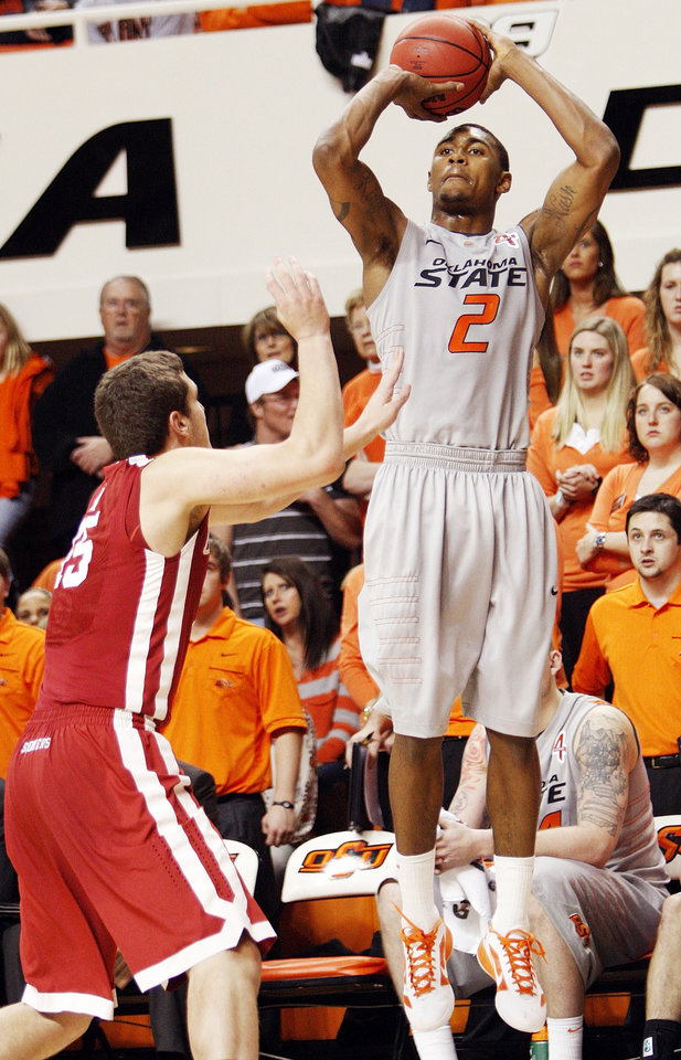 Photo - OSU's Le'Bryan Nash (2) shoots over Tyler Neal of OU in the second half during the Bedlam men's college basketball game between the Oklahoma State University Cowboys and the University of Oklahoma Sooners at Gallagher-Iba Arena in Stillwater, Okla., Monday, Jan. 9, 2012. OSU beat OU, 72-65. Photo by Nate Billings, The Oklahoman