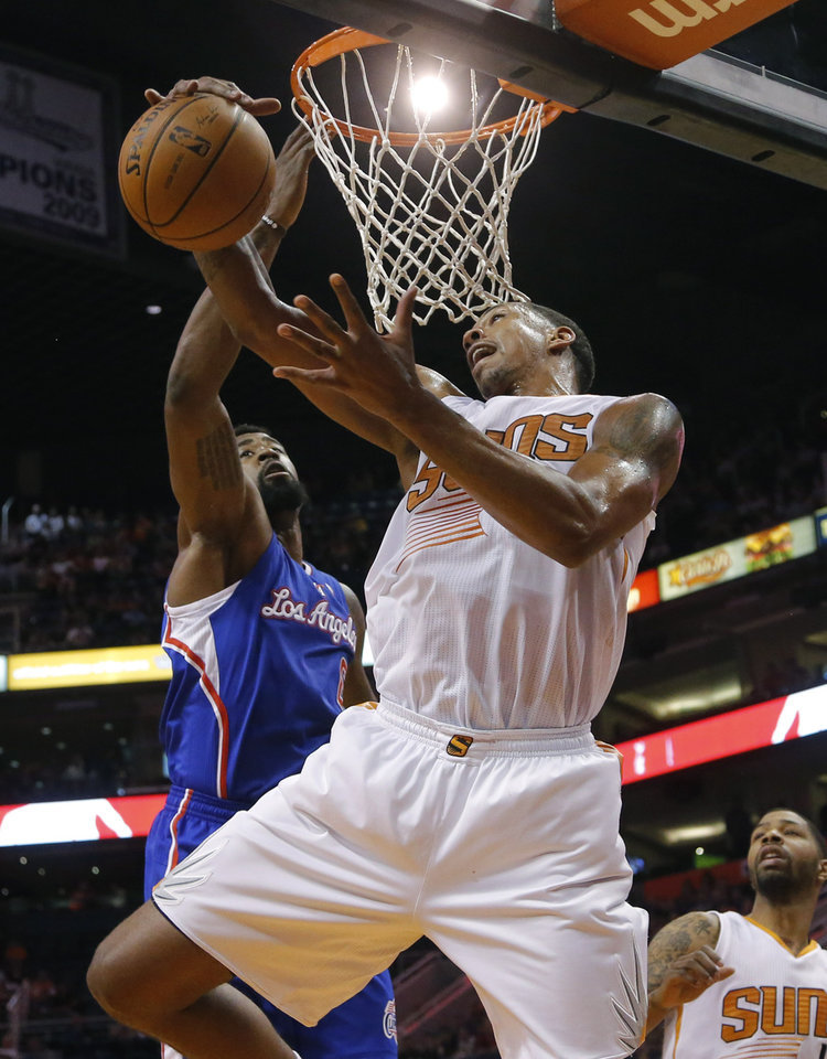 Photo - Los Angeles Clippers' DeAndre Jordan, rear, defends as Phoenix Suns' Channing Frye pulls down a rebound during the first half of an NBA basketball game, Tuesday, March 4, 2014, in Phoenix. (AP Photo/Matt York)