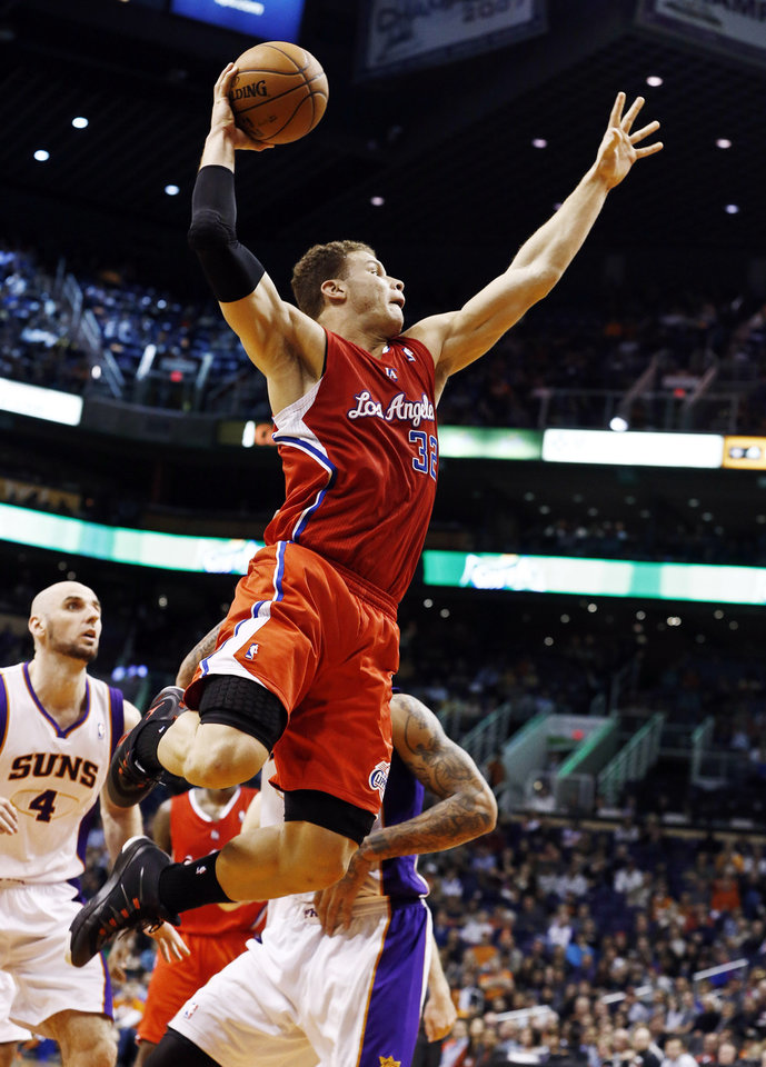 Los Angeles Clippers' Blake Griffin (32) dunks past Phoenix Suns' Marcin Gortat (4), of Poland, during the first half in an NBA basketball game, Thursday, Jan. 24, 2013, in Phoenix. (AP Photo/Ross D. Franklin)
