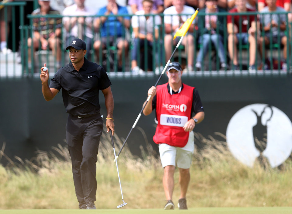 Photo - Tiger Woods of the US gestures to the crowd after putting out on the 3rd green as his caddie Ted Scott holds the flag during the second day of the British Open Golf championship at the Royal Liverpool golf club, Hoylake, England, Friday July 18, 2014. (AP Photo/Scott Heppell)