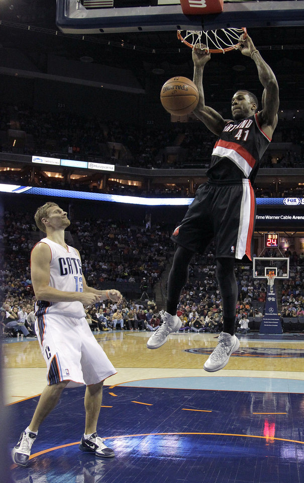 Photo - Charlotte Bobcats' Luke Ridnour (13) can only watch as Portland Trail Blazers' Thomas Robinson (41) dunks during the first half of an NBA basketball game in Charlotte, N.C., Saturday, March 22, 2014. (AP Photo/Bob Leverone)