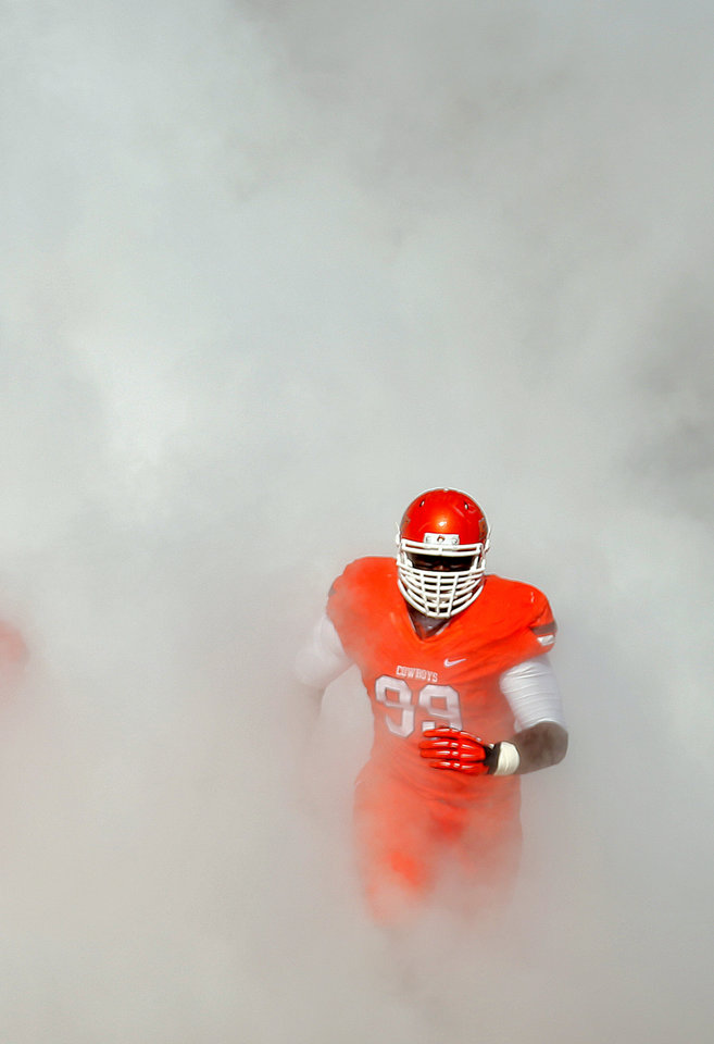 Oklahoma State's Calvin Barnett (99) runs onto the field during pre game introductions during a college football game between the Oklahoma State University Cowboys (OSU) and the Texas Christian University Horned Frogs (TCU) at Boone Pickens Stadium in Stillwater, Okla., Saturday, Oct. 19, 2013. Photo by Chris Landsberger, The Oklahoman