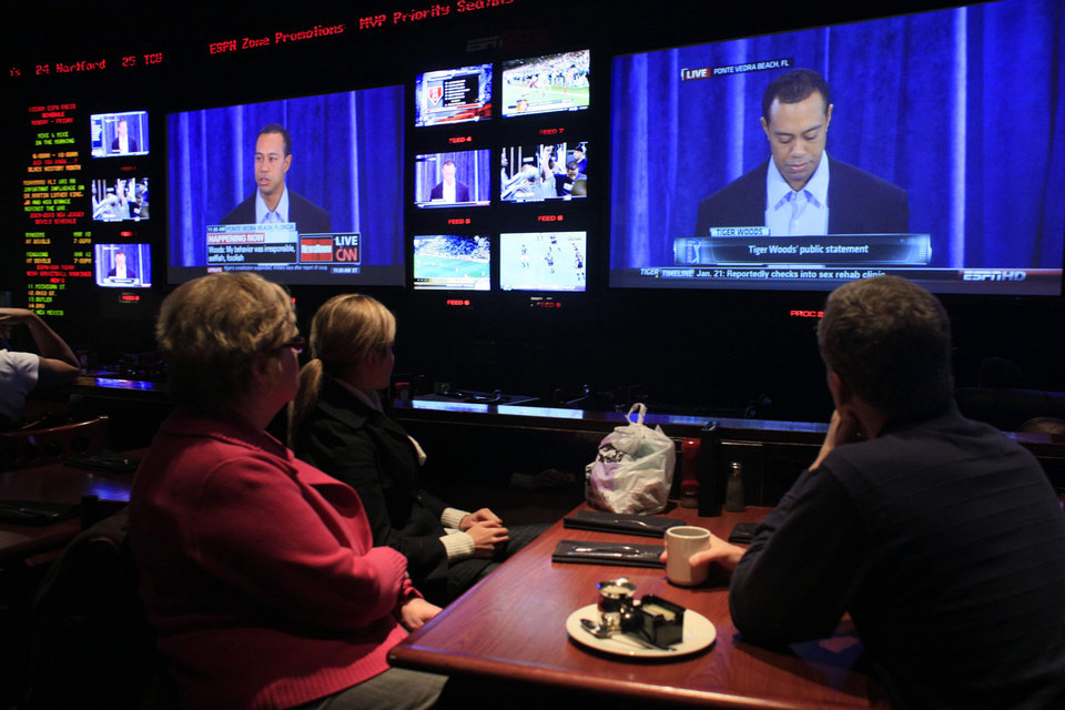 Photo - Krite, left, Colleen, center and Dan Kriste, of St. Louis Missouri, watch the Tiger Woods news conference at the ESPN Zone in Times Square, Friday, Feb. 19, 2010 in New York. Tiger Woods has apologized for having affairs and says he is unsure when he will return to competitive golf. (AP Photo/Mary Altaffer) ORG XMIT: NYMA101
