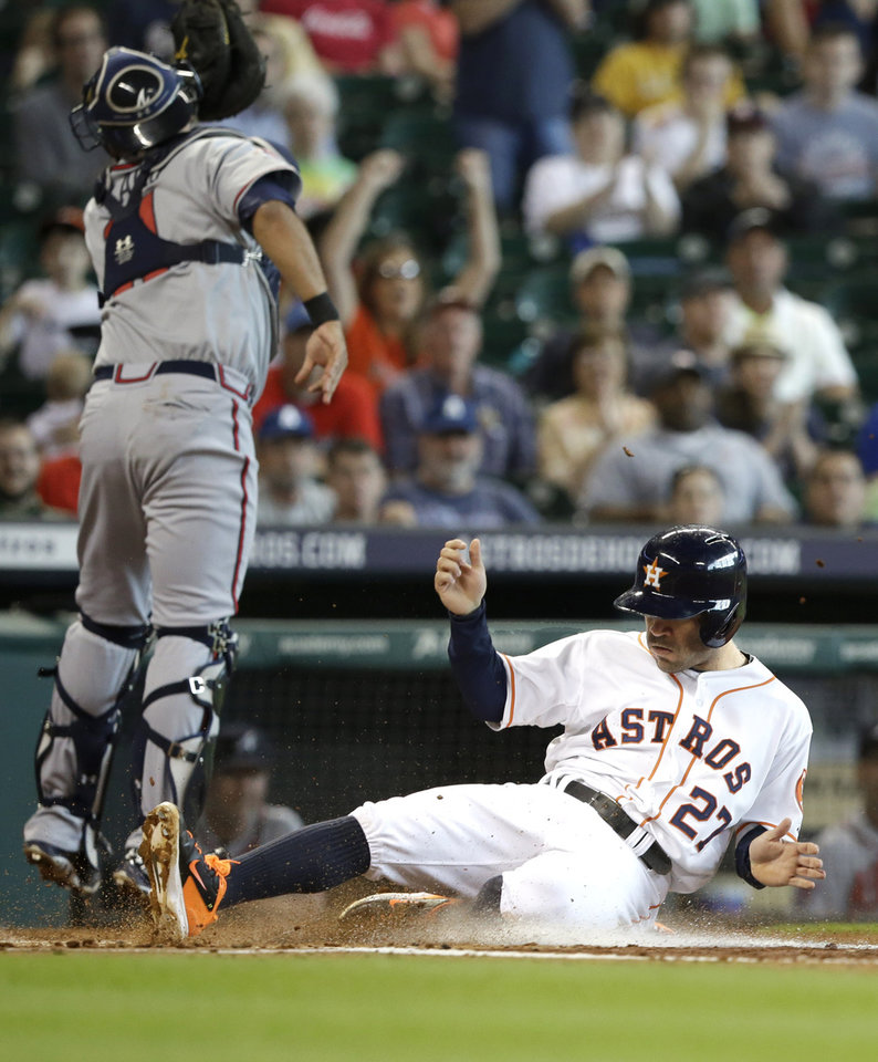 Photo - Houston Astros' Jose Altuve (27) slides safely across the plate to score as Atlanta Braves catcher Gerald Laird looks at the ball going past in the first inning of a baseball game Thursday, June 26, 2014, in Houston. (AP Photo/Pat Sullivan)