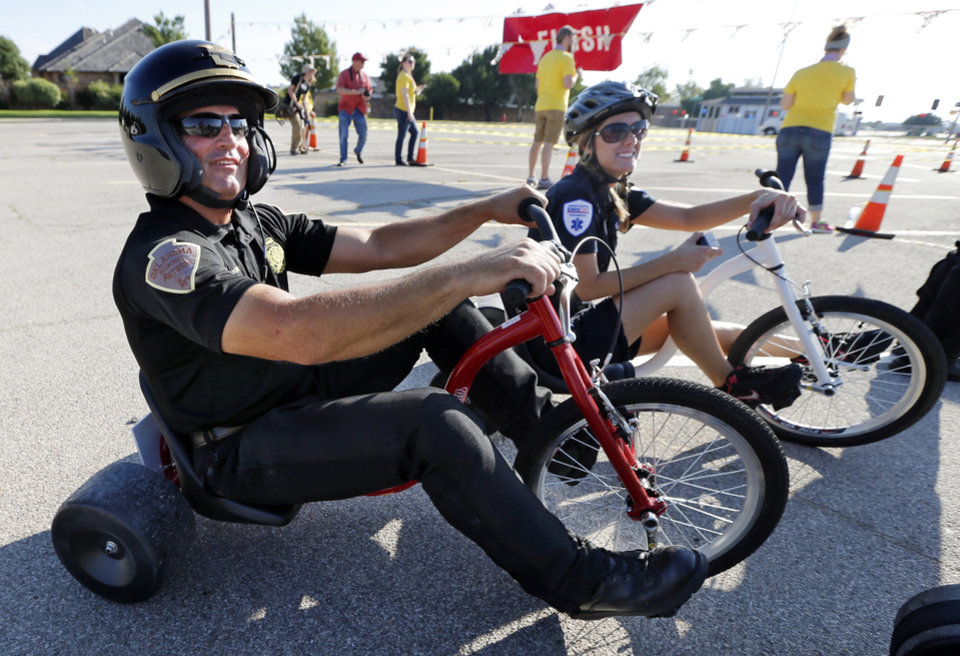 Photo -  Oklahoma Highway Patrol trooper Steve Johnson and EMSSTAT paramedic Melissa Denison finish their demonstration ride Saturday in Norman as children participate in The Ride, a race benefiting United Way. PHOTO BY STEVE SISNEY, THE OKLAHOMAN   STEVE SISNEY -