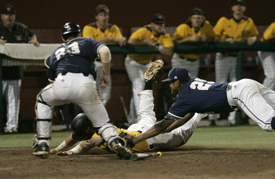 Photo - Kennesaw State's Chris McGowan is tagged out by Georgia Southern's pitcher Eric Alonzo on a sucide squeeze play as catcher Chase Grifin moves to block the plate in the eleventh inning of an NCAA regional college baseball game on Saturday,  May 31, 2014, in Tallahassee, Fla. Kennesaw State won the game 13-5.  (AP Photo/Steve Cannon)