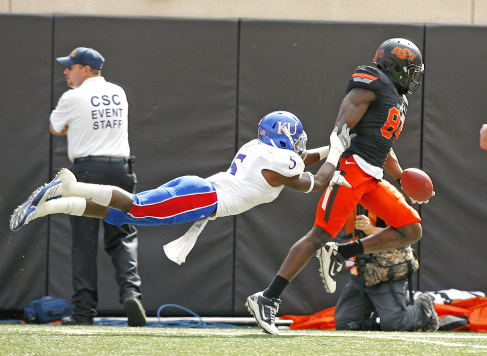 Photo - Kansas' Greg Brown (5) tries to stop Oklahoma State's Hubert Anyiam (84) near the goal line during a college football game between the Oklahoma State University Cowboys (OSU) and the University of Kansas Jayhawks (KU) at Boone Pickens Stadium in Stillwater, Okla., Saturday, Oct. 8, 2011 Photo by Steve Sisney, The Oklahoman