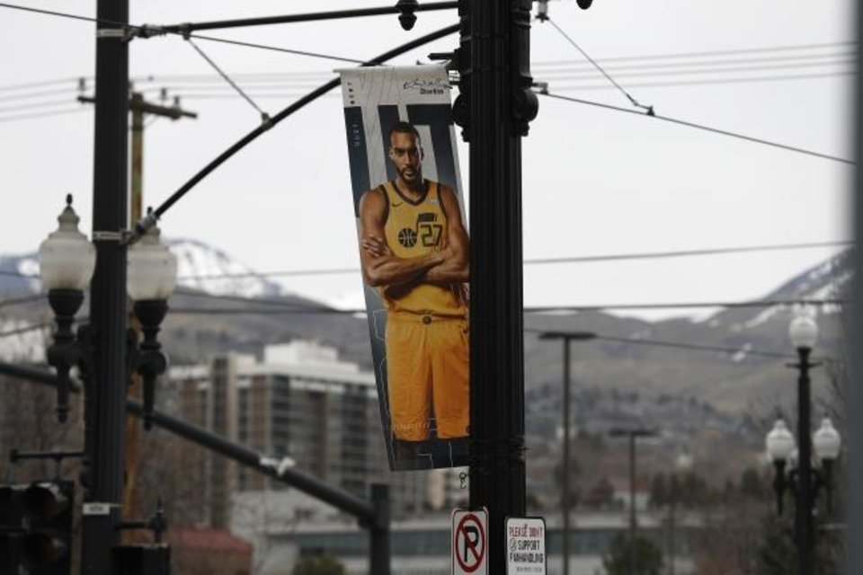 Photo -  A poster of Jazz center Rudy Gobert hangs near an empty main entrance at Vivint Smart Home Arena, where the Utah Jazz would have hosted the New Orleans Pelicans on Friday. [Jeffrey Swinger/USA TODAY Sports]