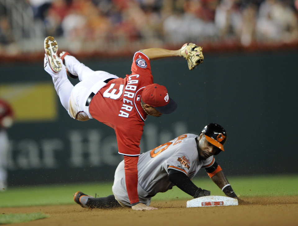 Photo - Baltimore Orioles' Adam Jones is out at second as Washington Nationals second baseman Asdrubal Cabrera (3) falls to the ground after turning a double-play on a grounder by Orioles' Nelson Cruz during the seventh inning of a baseball game, Monday, Aug. 4, 2014, in Washington. The Orioles won 7-3. (AP Photo/Nick Wass)