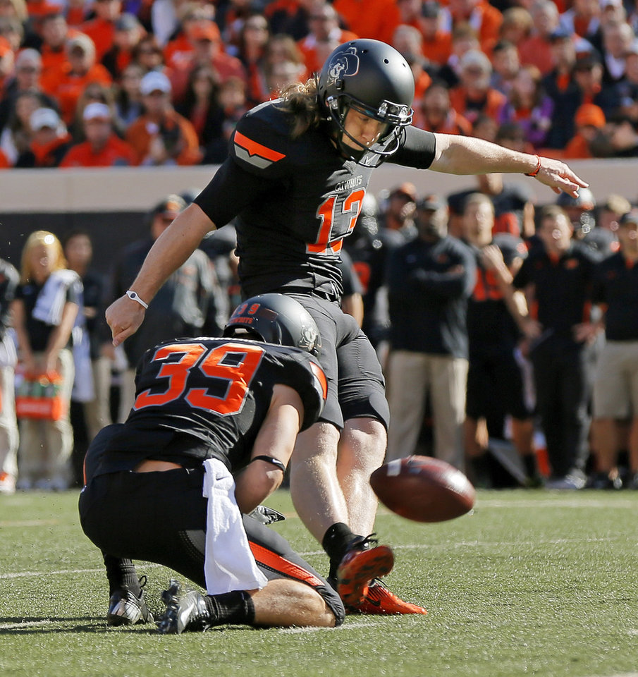 Photo - Oklahoma State's Quinn Sharp (13) kicks a field goal in the first quarter as Wes Harlan (39) holds during a college football game between Oklahoma State University (OSU) and Texas Christian University (TCU) at Boone Pickens Stadium in Stillwater, Okla., Saturday, Oct. 27, 2012. Photo by Nate Billings, The Oklahoman