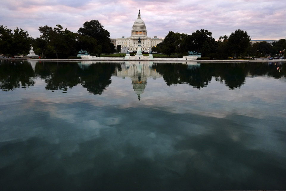 Photo - The Capital is mirrored in the Capital Reflecting Pool on Capitol Hill in Washington early Tuesday, Oct. 1, 2013. Congress plunged the nation into a partial government shutdown Tuesday as a long-running dispute over President Barack Obama's health care law stalled a temporary funding bill, forcing about 800,000 federal workers off the job and suspending most non-essential federal programs and services. (AP Photo/J. David Ake)