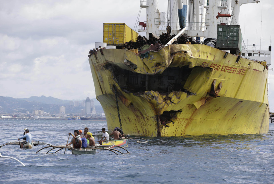 Photo - Volunteers search near the bow-damaged  cargo ship Sulpicio Express Siete Saturday Aug. 17, 2013, a day after it collided with a passenger ferry off the waters of Talisay city, Cebu province in central Philippines. Divers combed through a sunken ferry Saturday to retrieve the bodies of more than 200 people still missing from an overnight collision with a cargo vessel near the central Philippine port of Cebu that sent passengers jumping into the ocean and leaving many others trapped. At least 28 were confirmed dead and hundreds rescued. The captain of the ferry MV Thomas Aquinas, which was approaching the port late Friday, ordered the ship abandoned when it began listing and then sank just minutes after collision with the MV Sulpicio Express, coast guard deputy chief Rear Adm. Luis Tuason said. (AP Photo/Bullit Marquez)