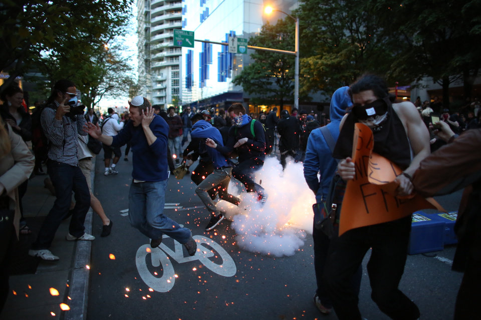 Protesters and media run from a police munition during a May Day protest in Seattle Wednesday May 1, 2013. Police used flash bangs and pepper spray against some protesters pelting them with objects late Wednesday, as a spurt of violence erupted after a May Day march for immigration reform ended. (AP Photo/Joshua Trujillo, seattlepi.com)