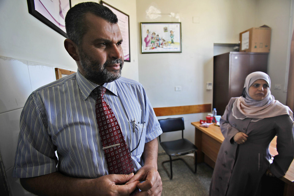 Photo - In this Tuesday, June 25, 2013 photo, Dr. Salah Rantisi, left, listens to a nurse at the baby test room at Khan Younis government clinic during an Interview in Khan Younis Refugee Camp, southern Gaza Strip. On the day of his induction, Baraa Rantisi, Salah's nephew, was told to wait near a mosque. A white car drove up. Secret passwords were exchanged. And then he was sworn into the Muslim Brotherhood, an exclusive movement that sees itself on a divine mission to establish Islamic rule. AP reporters got rare access to the Rantisi family, the closest thing to a royal clan in the Brotherhood in Gaza, at a time when the movement is under siege throughout the region. (AP Photo/Adel Hana)