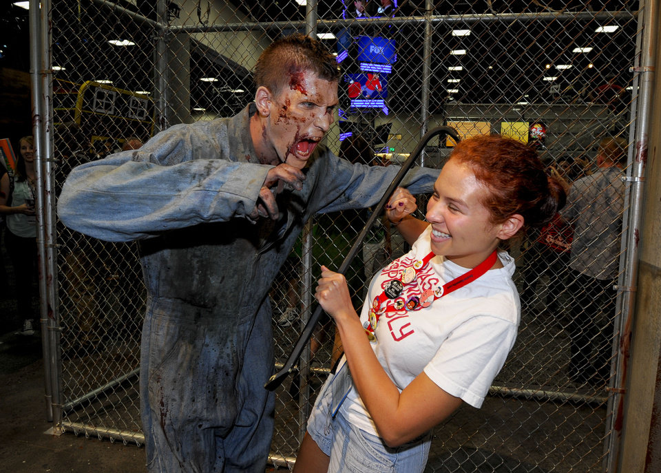 Photo - Olivia D'Agostino pulls a away from a zombie at AMC's Walking Dead booth during the Preview Night event on Day 1 of the 2013 Comic-Con International Convention on Wednesday, July 17, 2013 in San Diego. (Photo by Denis Poroy/Invision/AP) ORG XMIT: CADP112