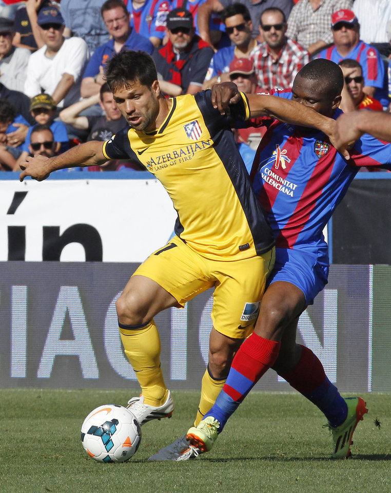 Photo - Atletico de Madrid's Leo Baptistao from Brazil, left, duels for the ball with Levante's Simao Mate from Mozambique during a Spanish La Liga soccer match at the Ciutat de Valencia stadium in Valencia, Spain, on Sunday May 4, 2014. (AP Photo/Alberto Saiz)