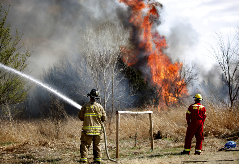 Photo - Firefighters battle a grassfire near a neighborhood at South County Line Road and S.W. 29th, Sunday, March 20, 2011, in Mustang, Okla.. Photo by Sarah Phipps, The Oklahoman