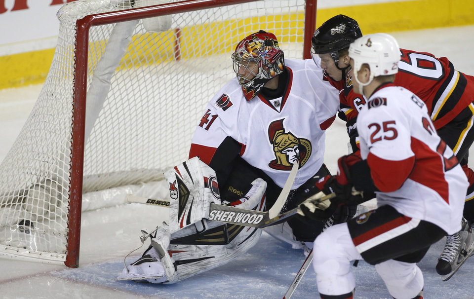 Photo - Ottawa Senators goalie Craig Anderson looks back at his net as Calgary Flames' Markus Granlund, of Finland, scores while Senators' Chris Neil (25) watches during the first period of an NHL hockey game Wednesday, March 5, 2014, in Calgary, Alberta. (AP Photo/The Canadian Press, Jeff McIntosh)
