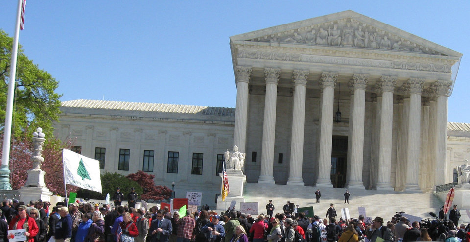Photo - Demonstraters march in front of the U.S. Supreme Court on Tuesday as justices hear oral arguments in a case about the 2010 federal health care law.  Chris Casteel - The Oklahoman