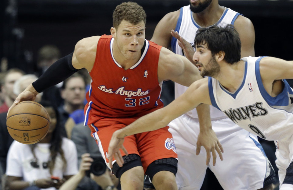 Photo - Minnesota Timberwolves' Ricky Rubio of Spain, right, lunges for the ball as Los Angeles Clippers' Blake Griffin keeps it away in the first half of an NBA basketball game Wednesday, Jan. 30, 2013 in Minneapolis. (AP Photo/Jim Mone)