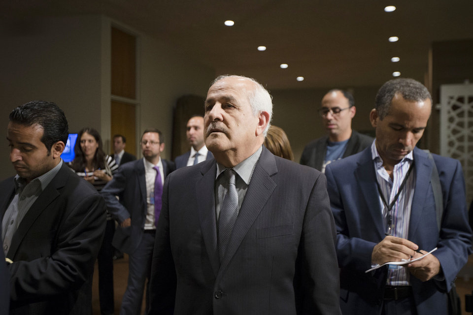 Photo - Palestinian U.N. Ambassador Riyad Mansour listens as Rwandan U.N. Ambassador Eugene Gasana speaks outside an emergency meeting of the U.N. Security Council on the worsening situation in Gaza at United Nations headquarters, Sunday, July 20, 2014. A Jordan-drafted resolution obtained by The Associated Press expresses