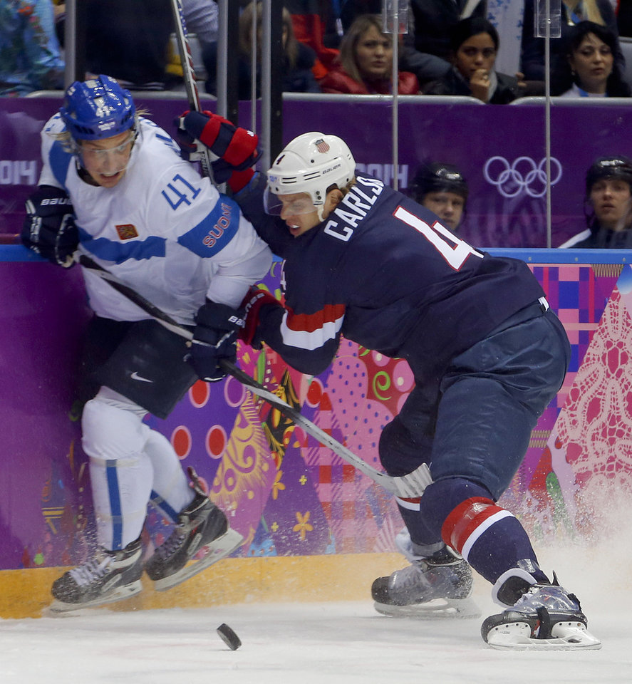 Photo - Finland forward Antii Pihlstrom and USA defenseman John Carlson crash the boards during the first period of the men's bronze medal ice hockey game at the 2014 Winter Olympics, Saturday, Feb. 22, 2014, in Sochi, Russia. (AP Photo/Petr David Josek)