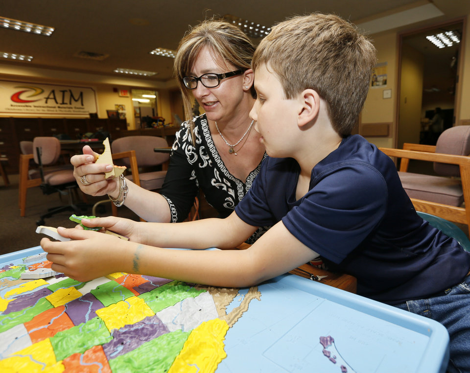 Photo -  Teague Niebrugge and his mother, Joey Niebrugge, use a tactile map of the United States at the Oklahoma Library for the Blind and Physically Handicapped, 300 NE 18. Teague Niebrugge will be attending the upcoming BELL (Braille Enrichment for Literacy and Learning) camp. Photo by Nate Billings, The Oklahoman   NATE BILLINGS -  NATE BILLINGS